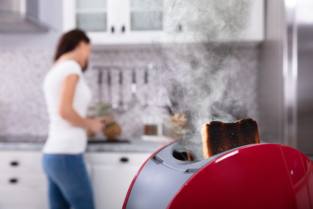 Close-up Of A Red Toaster With Burnt Toast While Woman Working In Kitchen
